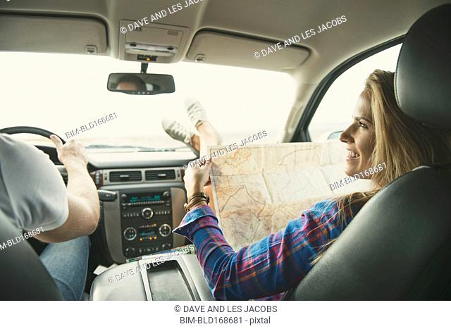 Caucasian couple riding in car using map
