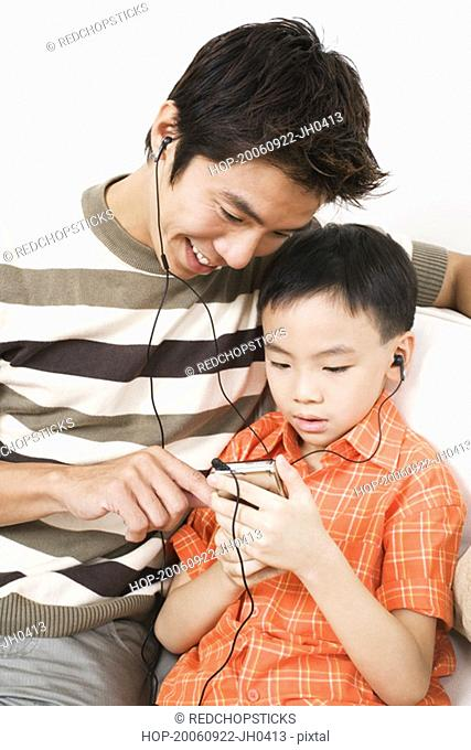 Close-up of a mid adult man and his son listening to an MP3 player