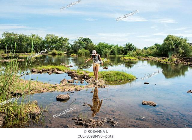 Young female tourist exploring calm waters near Victoria Falls, Zimbabwe, Africa