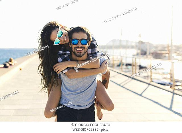 Happy couple at the harbour, man carrying wman piggyback