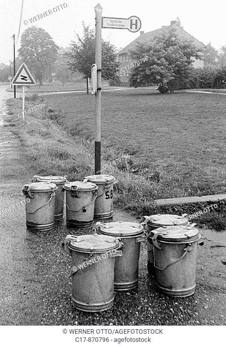 Seventies, black and white photo, humour, product photography, eight dustbins stand at a bus stop waiting for collection