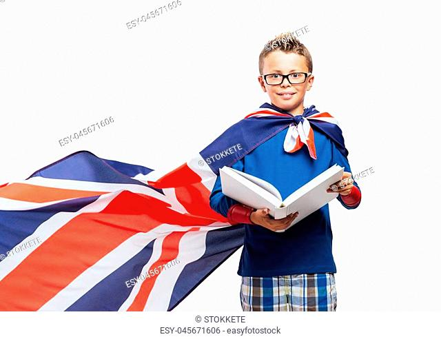 Cute superhero boy reading a book, he is wearing a British flag as a cape, education and enjoyment concept