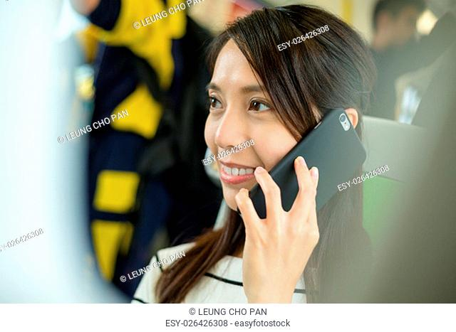 woman talk to cellphone inside train compartment