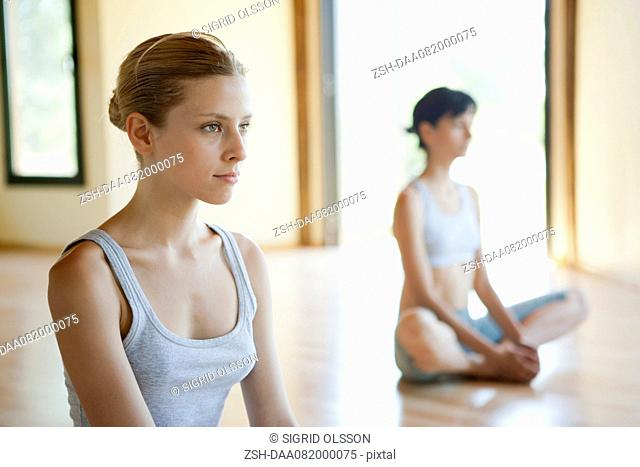 Young woman sitting in lotus position in yoga class