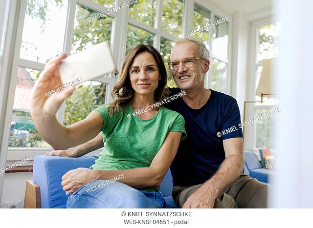 Smiling mature couple taking a selfie at home