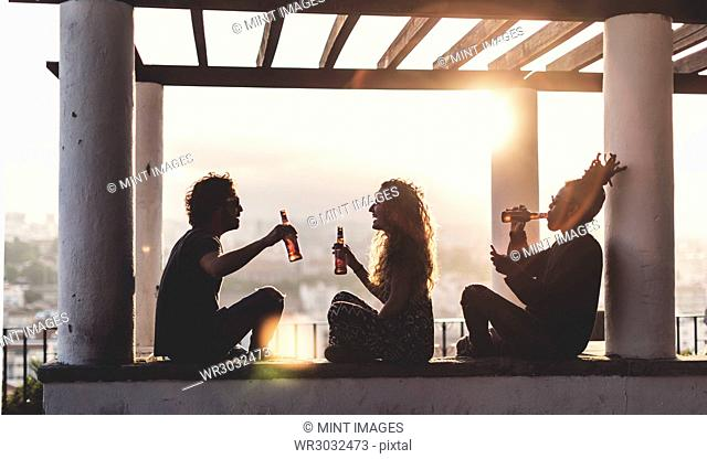 Silhouette of two men and a woman sitting outdoors under a pergola at sunset, holding beer bottles