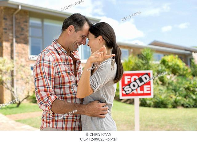 Couple hugging outside new house