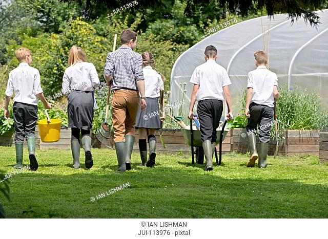 Teacher and middle school students with wheelbarrow learning gardening in vegetable garden