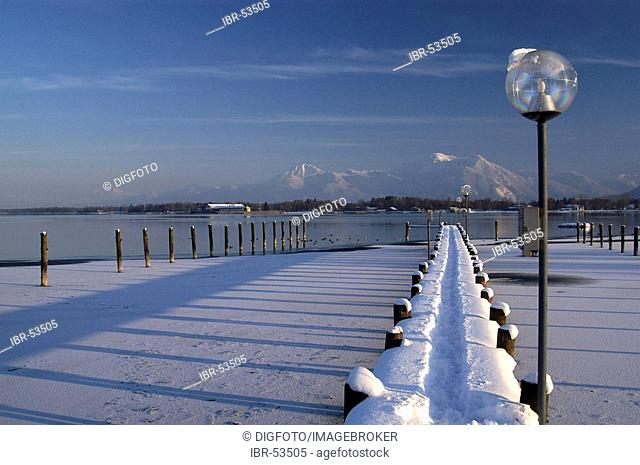 Snowy landing stage and lantern in front of Hochgern and Hochfelln, Lake Chiemsee, Bavaria, Germany