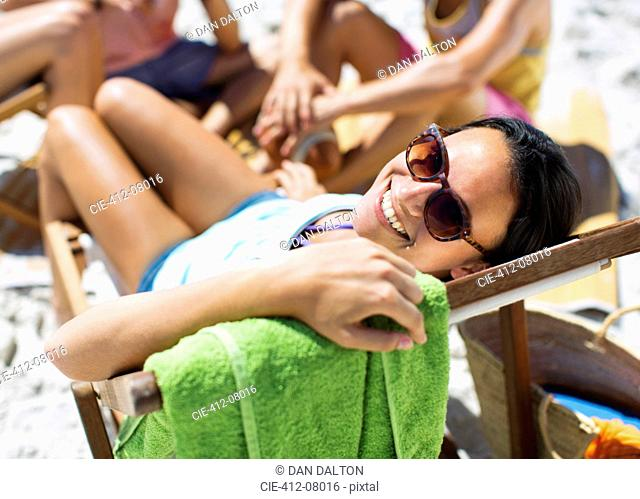 Portrait of happy woman sitting in lounge chair on beach