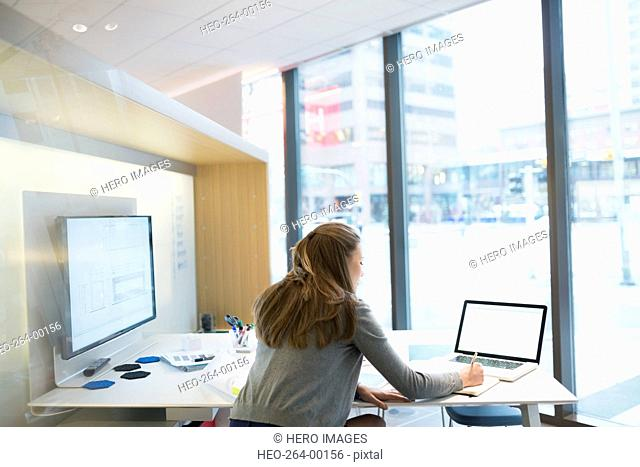 Young businesswoman using laptop in urban office