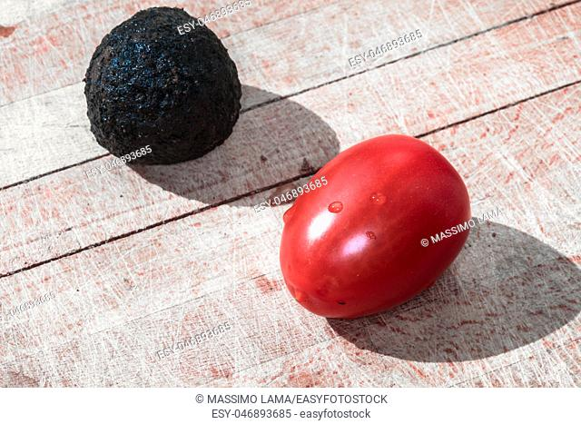Tomato and black truffle isolated on a wooden cutting board