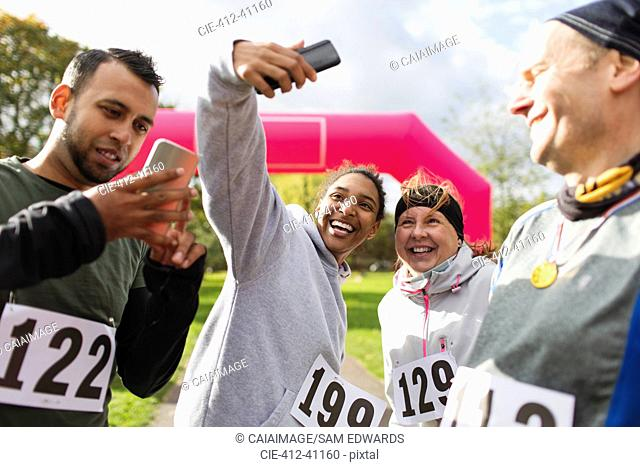 Happy runner friends taking selfie with camera phone at charity run in park