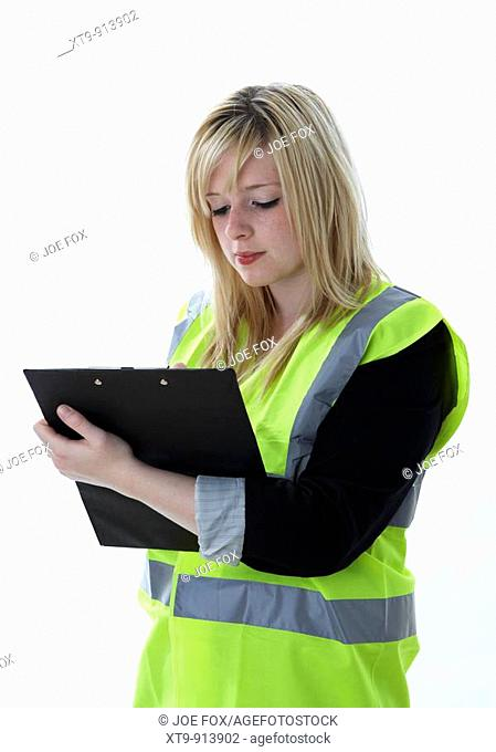 young 20 year old blonde woman wearing a high vis vest concentrating writing on a clipboard