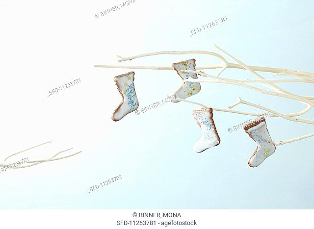 Boot-shaped iced biscuits hanging on a light coloured twig