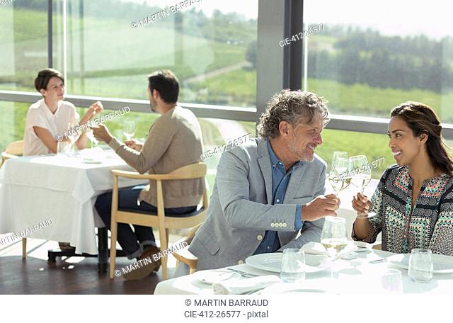Couple toasting wine glasses in sunny winery dining room