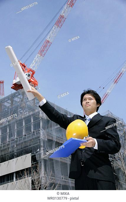 A mid adult businessman standing at construction site
