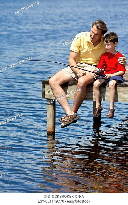 Father Fishing With His Son On A Pier