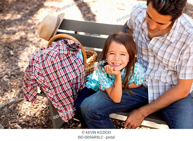 Portrait of girl in community garden sitting on bench with father
