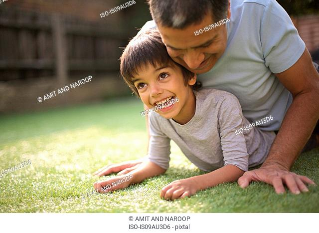 Father in garden lying on top of smiling boy