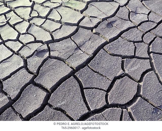 Cracked mud forms deep grooves, caused by the lack of rain and the severe drought suffered by the Peninsular Northwest. Image in the Portomarin reservoir