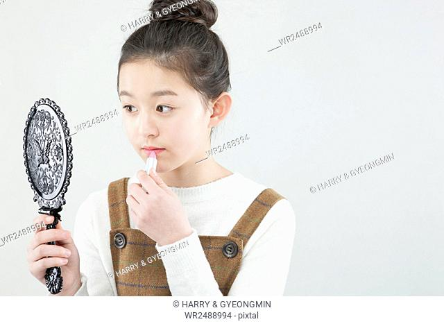 Side view portrait of Korea school girl holding a hand mirror and putting on make-up