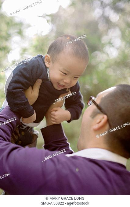 USA, Father holding aloft son (2-3) in park