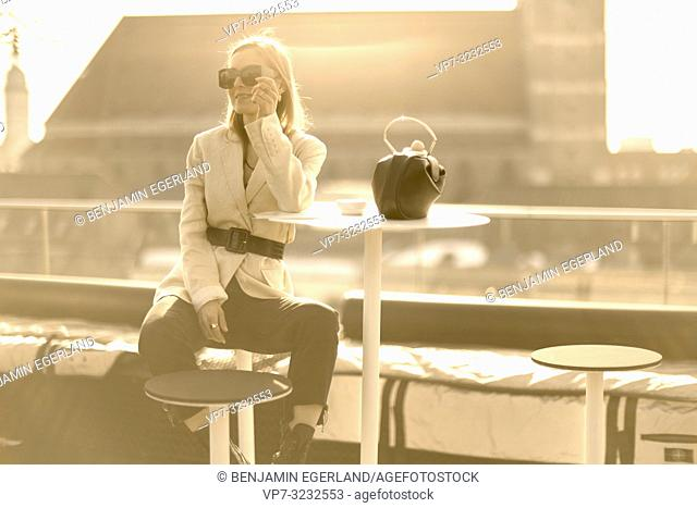 fashionable blogger woman taking break outdoors at balcony in city, in Munich, Bavaria, Germany