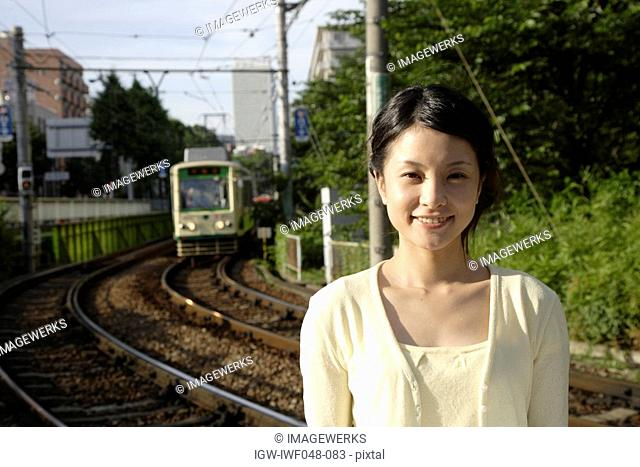 Portrait of a young woman with train in background