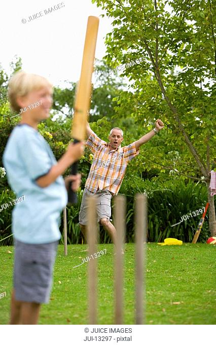 Boy 10-12 playing cricket with father
