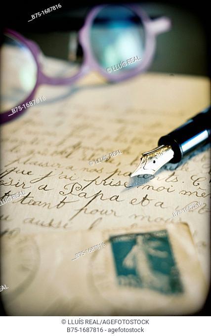 carta antigua manuscrita con sello de correos, pluma estilografica y gafas, old handwritten letter postmarked, pen stylographic and glasses