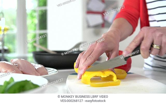 Close up of woman cutting yellow pepper before adding to frying pan.Shot on Sony FS700 in PAL format at a frame rate of 25fps