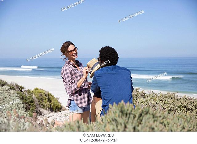 Smiling multi-ethnic couple talking on sunny summer beach