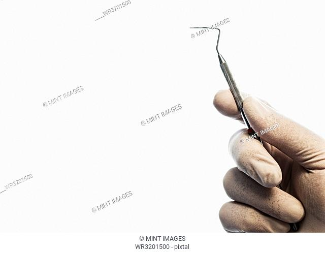 Closeup of a hand holding a dental probe