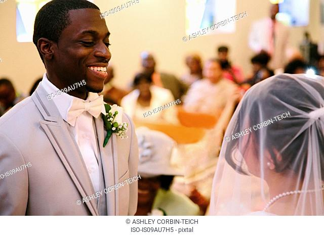 Bridegroom in church wedding ceremony smiling at bride