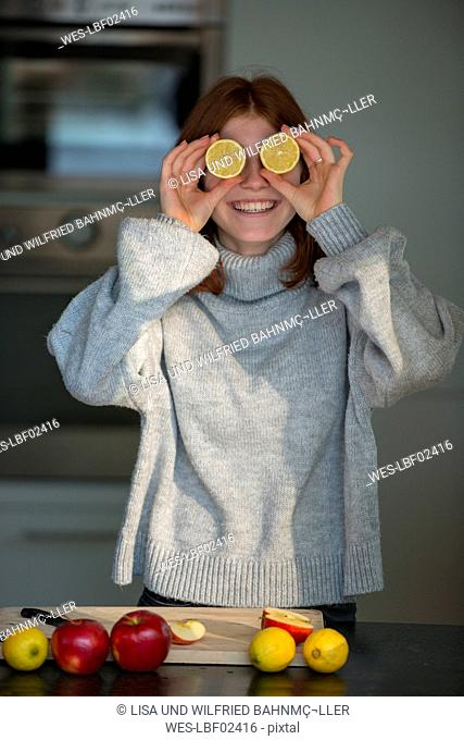Laughing teenage girl holding lemon halves in front of her eyes