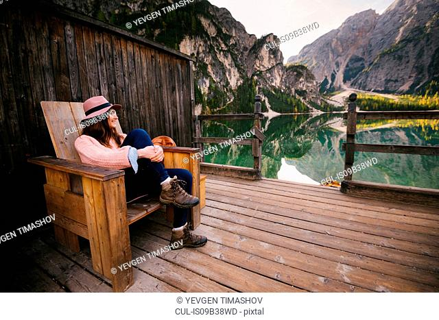 Woman relaxing on wooden chair, Lago di Braies, Dolomite Alps, Val di Braies, South Tyrol, Italy
