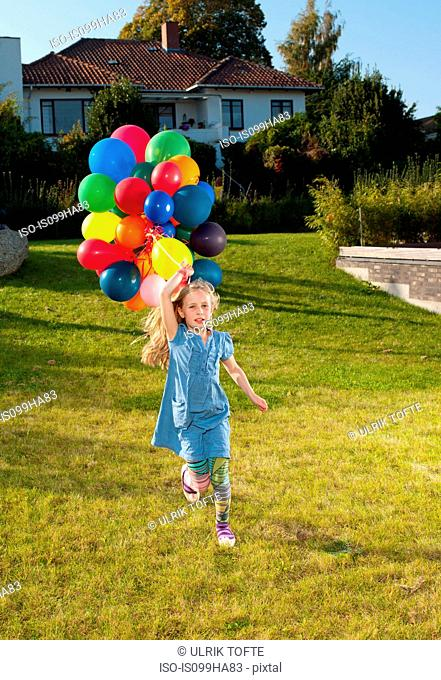 Girl running across lawn with multicoloured balloons