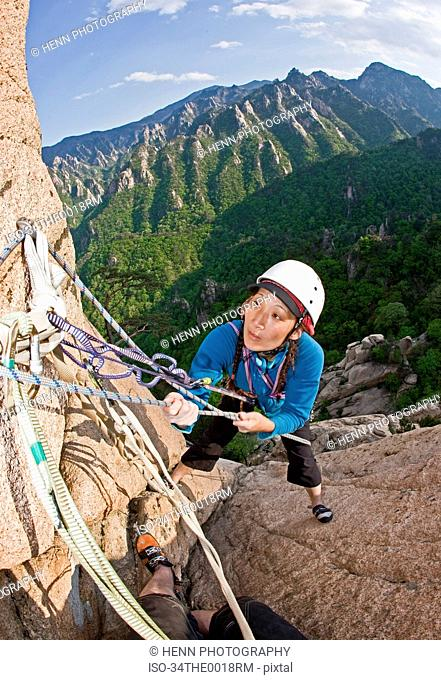 Woman climbing rocky mountainside
