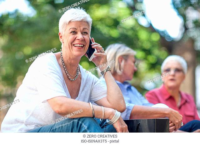 Senior woman chatting on smartphone in city
