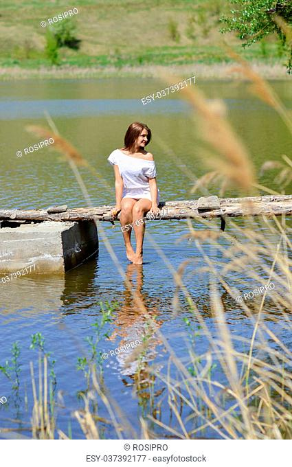Happy young woman in white dress sitting on pier by river or lake