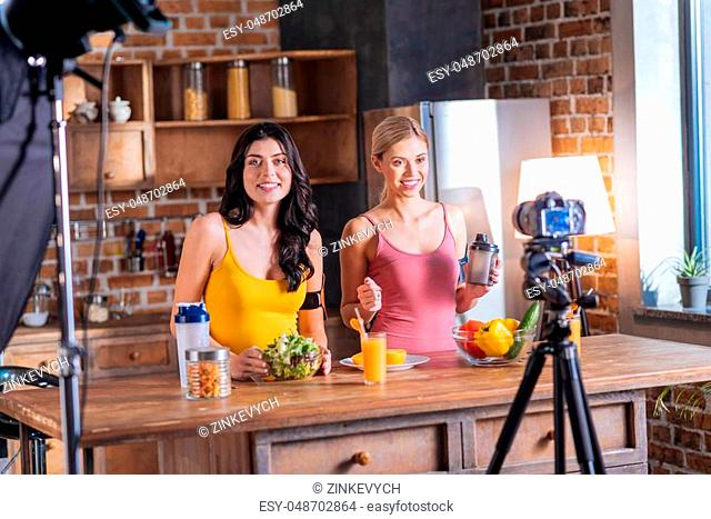 Healthy lifestyle. Cheerful nice female bloggers smiling and recording a video while promoting healthy lifestyle