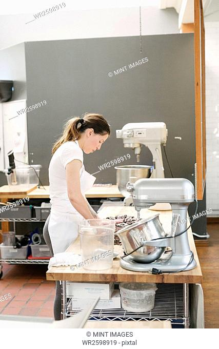 Woman wearing a white apron standing at a work counter in a bakery