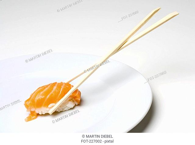 Wooden chopsticks holding salmon sushi piece