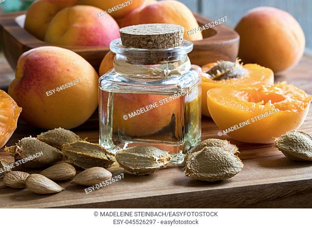 A bottle of apricot kernel oil with ripe apricots and apricot kernels on a wooden table