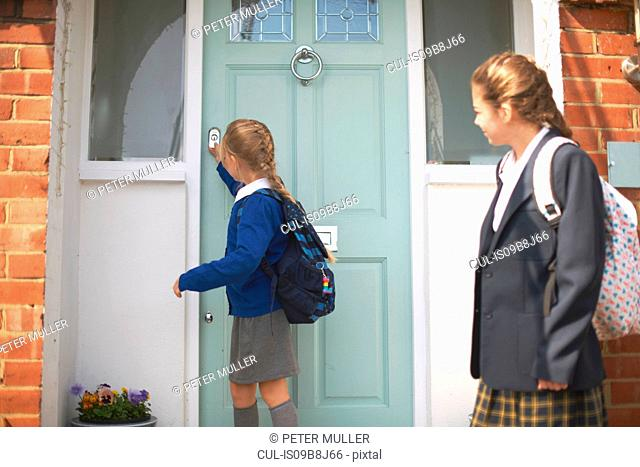 School girl and teenage sister closing front door