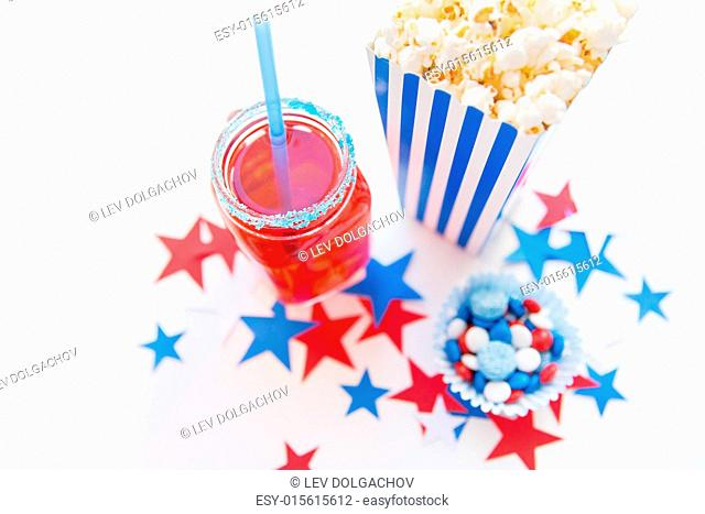 american independence day, celebration, patriotism and holidays concept - close up of juice glass or mason jar, popcorn and candies with stars confetti...