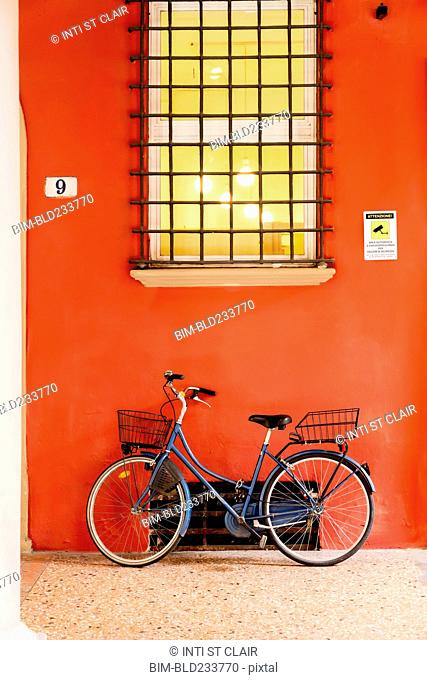Blue bicycle leaning on orange wall under window