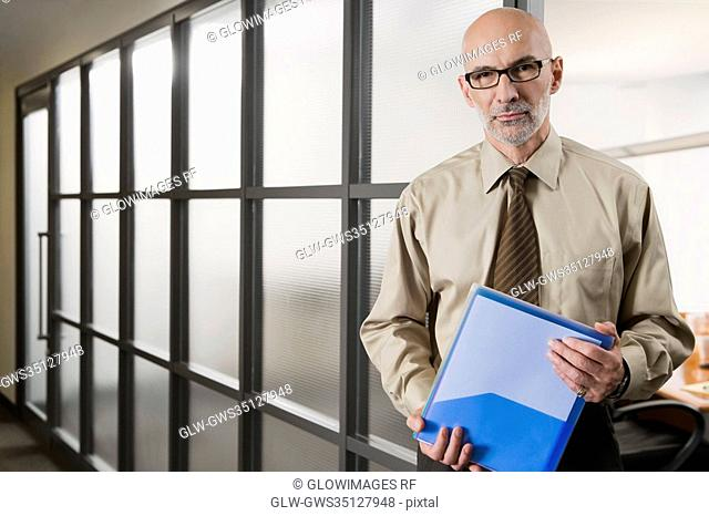 Portrait of a businessman holding a file