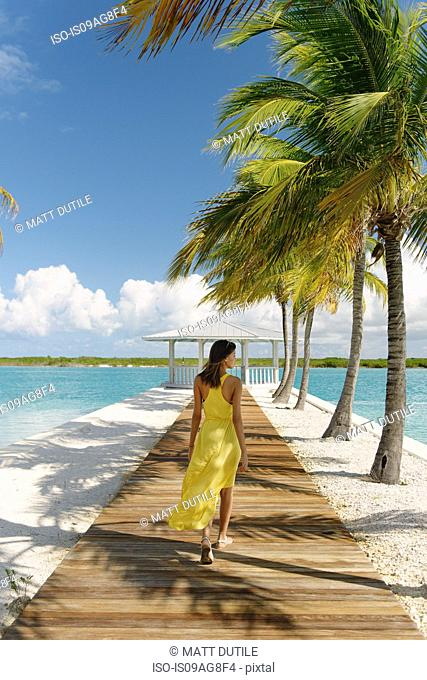Young woman strolling on beach pier, Providenciales, Turks and Caicos Islands, Caribbean